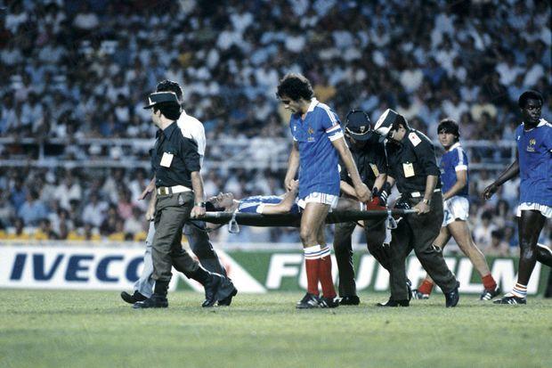 Michel Platini accompagne la civière sur laquelle gît Patrick Battiston, qui tombera dans le coma après avoir été percuté par le joueur allemand Harald Schumacher lors de la demi-finale de la Coupe du monde 1982 à Séville.