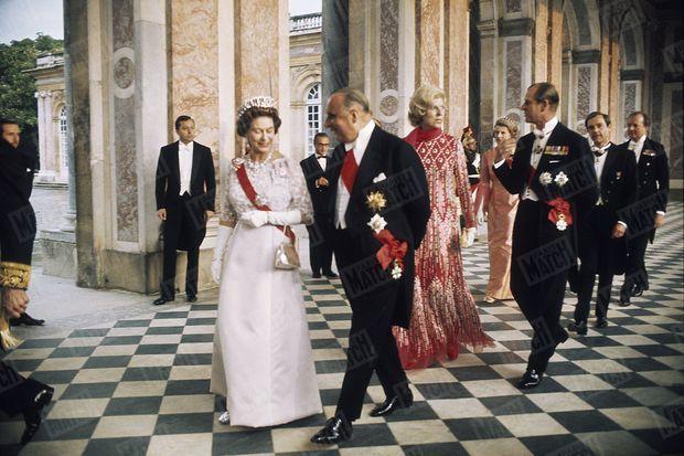 15 mai 1972. Décorum royal à Versailles. Le couple présidentiel fait à la reine Elizabeth II d'Angleterre et à son mari le prince Philip les honneurs du palais du Grand Trianon. Cette photographie de François Pagès, prise avant le somptueux dîner de gala en l'honneur de Sa Majesté, permet de mesurer tout le faste de la rencontre. Le séjour de la reine et de son époux se déroule sans accrocs, au grand soulagement de Claude Pompidou, toute de Dior vêtue pour cette soirée, autant de symboles de l'excellence de la relation franco-britannique qui est marquée par l'adhésion du Royaume-Uni à la Communauté européenne de 1973.