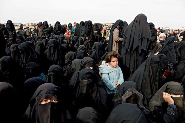 Premier arrêt à la sortie de Baghouz sur un plateau désertique... au cas où une bombe exploserait. Les femmes et les enfants reçoivent des vivres de l'ONG Free Burma Rangers