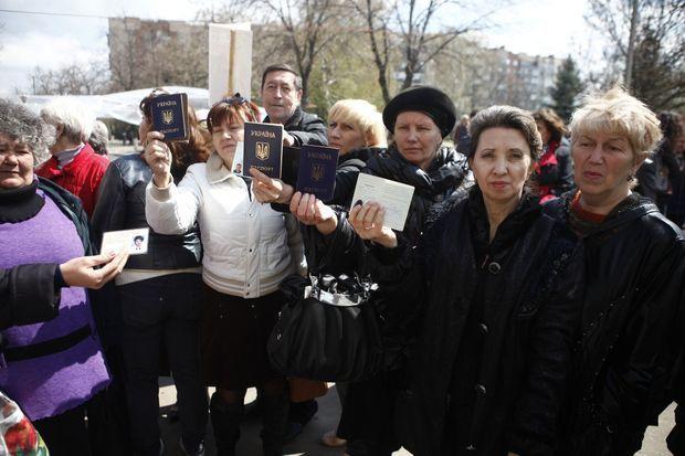 Brandisant leur passeport ukrainien, Natalya (au centre à droite) et d'autre résidentes de Slaviansk qui se sont portées volontaires pour faire bouclier humain devant les barricades des autonomistes de Slaviansk le mardi 15 avril 2014, à l'est de l'Ukraine.