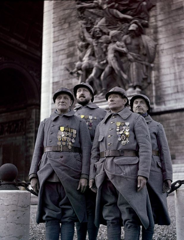 Quatre poilus au garde-à-vous devant la flamme de la tombe du soldat inconnu, sous l'Arc de triomphe, le 11 novembre 1951.