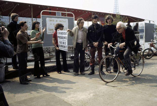 « René Dumont dans la lutte antipollution : c'est à bicyclette qu'il gagne chaque jour son P.C. flottant, une péniche au pont de l'Alma. » - Paris Match n°1304, 4 mai 1974