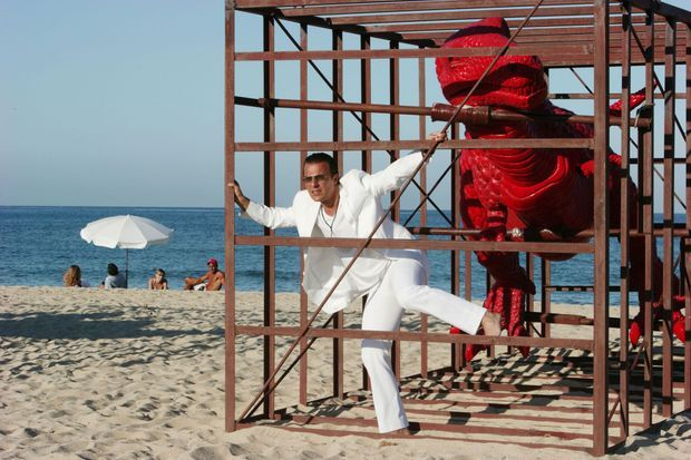 Jean Roch alias Jean-Roch Pedri, vêtu de blanc, pieds nus, dans une cage où est exposé un des dinosaures que l''artiste Sui Jianguo expose sur la plage de Pampelonne.