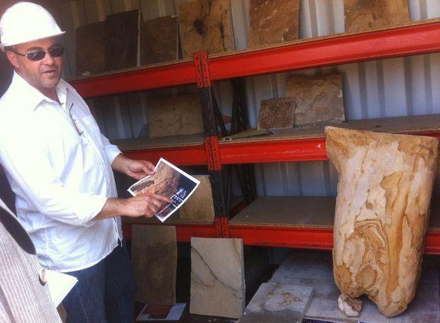 Le directeur du chantier, Richard Buffat, tient une photo de la grotte originale où sont portées les indications colorimétriques utilisées par les artisans et les artistes qui respectent les teintes de la roche.