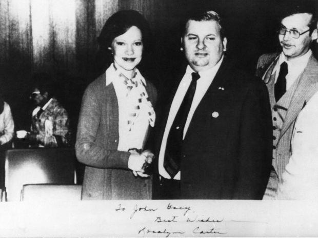 """En 1975, Gacy est devenu directeur du défilé annuel de la communauté polonaise de Chicago. C'est dans ce cadre que le tueur en série a rencontré la First Lady, Rosalynn Carter, épouse du président américain Jimmy Carter, le 6 mai 1978. La photo prise ensemble lui a été dédicacée par la Première dame : """"À John Gacy, meilleurs voeux - Rosalynn Carter."""""""