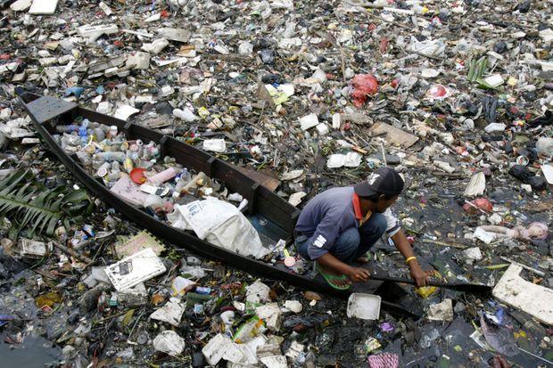 Un Indonésien sur sa barque navigue au milieu de déchets.