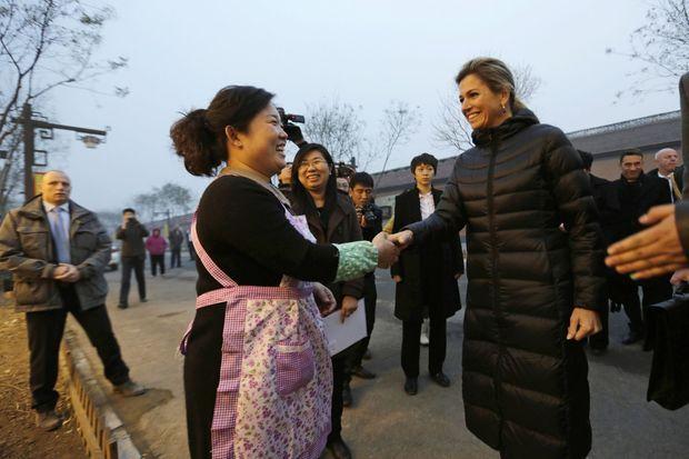 La reine Maxima des Pays-Bas avec une villageoise alors qu'elle visite son restaurant de nouilles, le 26 novembre 2014