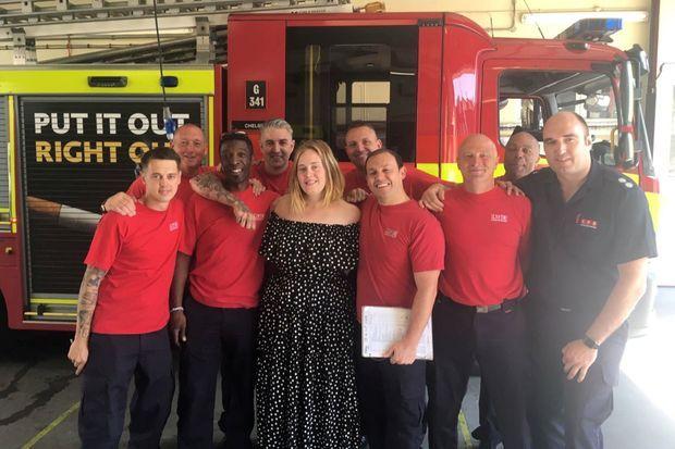 Adele rend visite aux héros de l'incendie, à Londres.
