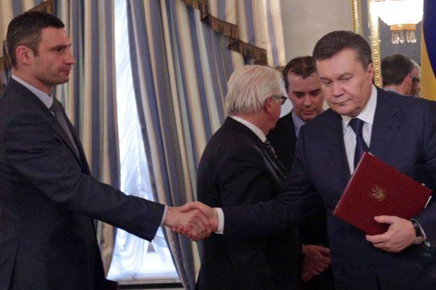 Le chef de l'Etat ukrainien et le chef de l'opposition se serre la main après la signature de l'accord
