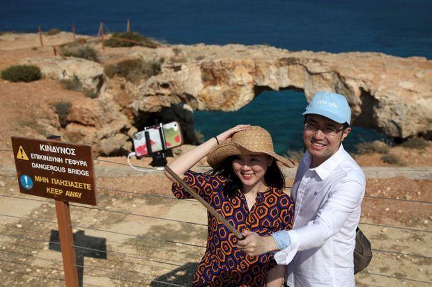 Deux personnes se prennent en selfie devant une falaise.