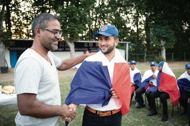 Prebou Balane, président de France Cricket, avec Shahid. Avant le départ pour les Pays-Bas, chaque joueur reçoit un drapeau français.