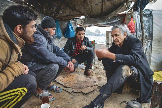 """BHL avec des réfugiés syriens. En 2019, ils étaient moins de 10% dans ce """"hot spot"""" financé par l'Europe mais géré par la Grèce."""