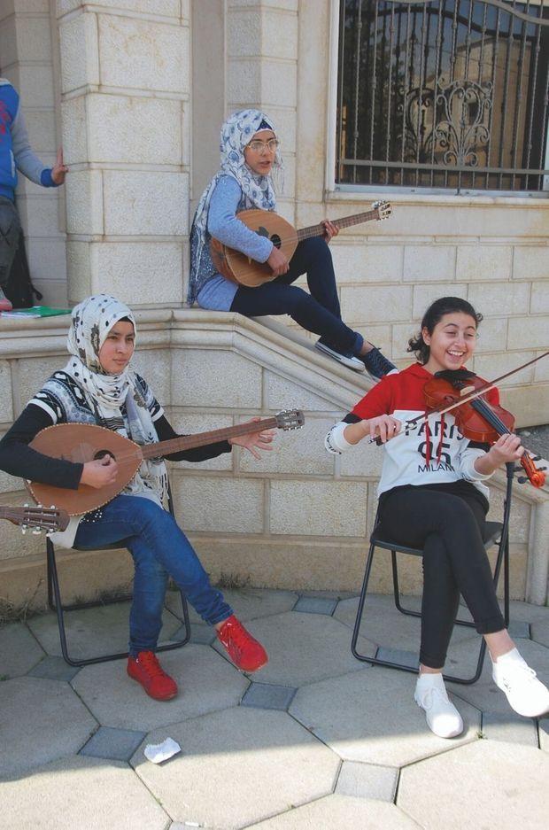 Profitant d'une pause, trois élèves entonnent des chants traditionnels