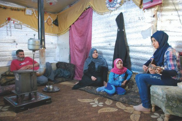 Hida, 14 ans, répète ses morceaux de bouzouk dans la tente familiale. Son rêve : rejoindre un orchestre professionnel.