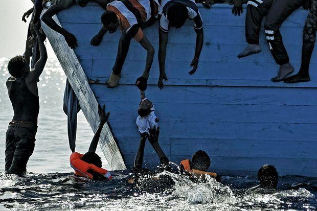 Sous l'effet de la panique, des migrants ont sauté à l'eau. Ils tentent de regagner le bateau.