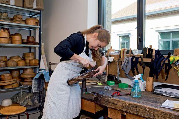 Elodie, chapelière de la maison Michel. Derrière elle, s'entassent plus de 3 000 formes en bois.