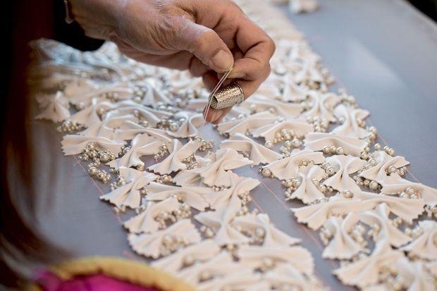 Des pigments blancs sont déposés et fixés sur le tissu grâce à un calque piqué faisant apparaître le point exact où la perle devra être cousue.