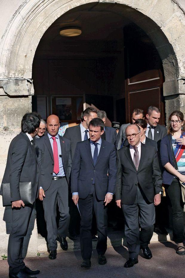 Manuel Valls et le ministre de l'Intérieur, Bernard Cazeneuve, sortent de l'église Saint-Cyr-Sainte-Julitte à Villejuif, mercredi 22 avril.