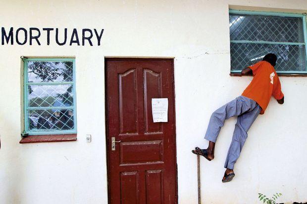 Le 4 avril, à Garissa. Un homme tente d'apercevoir, par la fenêtre de la morgue, les corps des quatre terroristes abattus par le Recce, les forces spéciales kényanes.