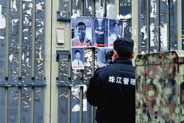 Un agent de sécurité décolle les affiches à la gloire des médecins lanceurs d'alerte, dont Li Wenliang, décédé du Covid.