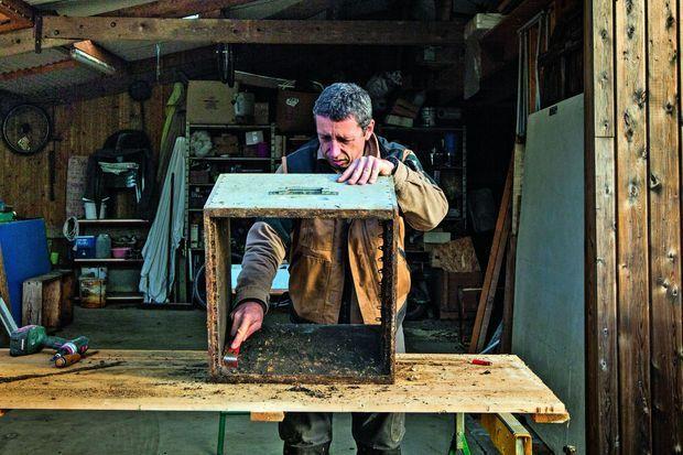 L'apiculteur nettoie et désinfecte ses ruches, soucieux d'éliminer le moindre risque de maladie.