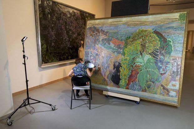 """""""L'été. La danse"""", de Pierre Bonnard (1912, huile sur toile, 202x254 cm). A l'aide d'une lampe à constat, Véronique Roca, conservatrice-restauratrice, vérifie l'état de la toile venue de Moscou."""