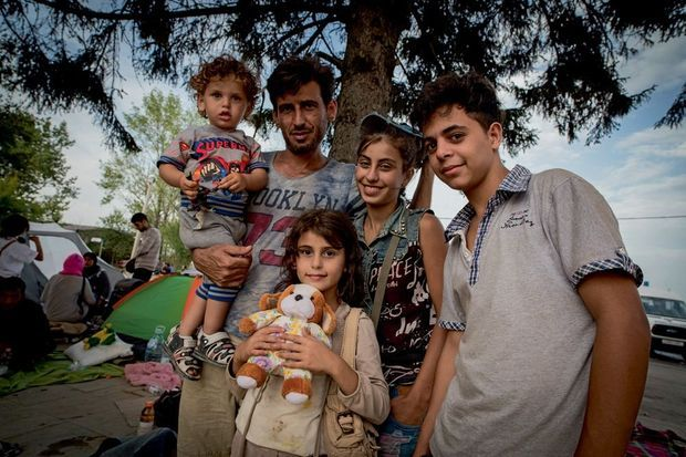 Mohamed, 13 ans (à dr.), avec Mahmoud (au centre) et trois de ses enfants. Parti seul de Syrie il y a deux semaines, l'adolescent a été recueilli par cette famille originaire de Homs.
