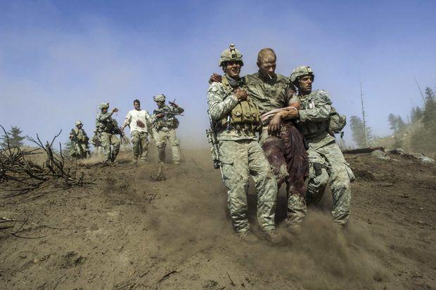 Afghanistan. Des soldats de la 173e brigade aéroportée évacuent deux camarades blessés lors d'une embuscade tendue par les talibans, dans la vallée de Korengal, le 23 octobre 2007.