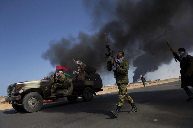 Libye. Lance-roquettes à la main, les rebelles se retirent du port pétrolier de Ras Lanouf, le 11 mars 2011, alors que les troupes de Kadhafi viennent de le reprendre. Cinq jours plus tard, la photographe et trois autres journalistes sont kidnappés par des loyalistes. Ils seront relâchés au bout de deux jours.