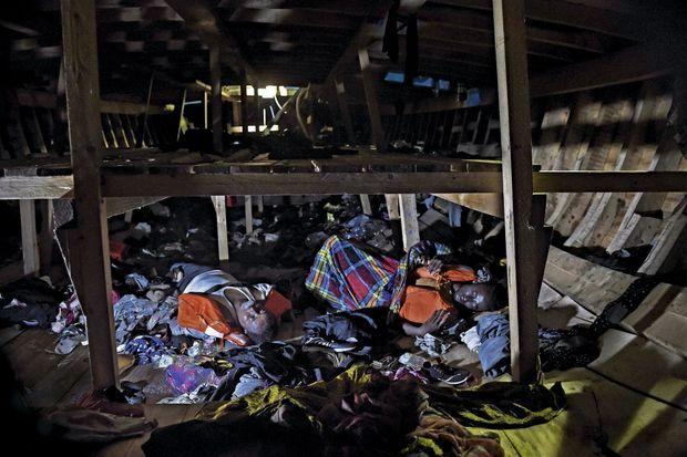 Deux des trois hommes retrouvés sans vie à bord du bateau repéré par l'« Astral », le navire affrété par l'ONG espagnole Proactiva Open Arms, le 4 octobre. En médaillon : sous l'effet de la panique, des migrants ont sauté à l'eau. Ils tentent de regagner le bateau.