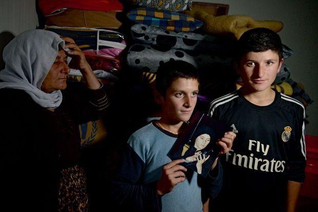 Dans le camp de réfugiés de Qad Ya, en Irak, le 1er décembre 2015. Kamila, 51 ans, avec ses deux fils Khayat, 11 ans, et Kakhib, 14 ans. Entre les mains du plus jeune, une photo de lui quand il était au service de Daech.