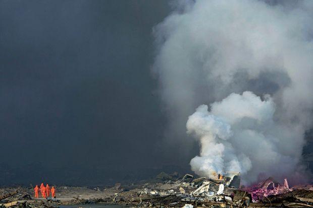Près de l'incendie principal, des militaires chinois en combinaisons NBC, censées protéger des armes nucléaires, biologiques et chimiques, jeudi 13 août.