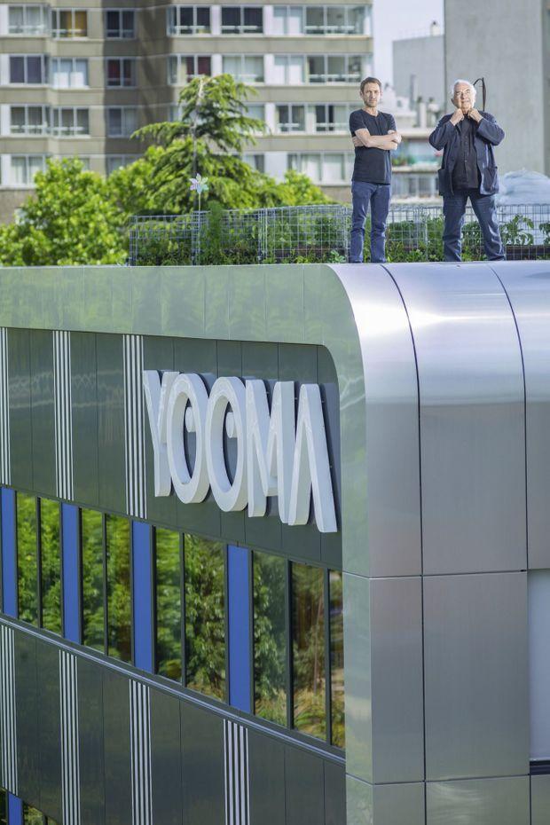 Ora Ïto (à g.) et Daniel Buren sur le toit de l'hôtel, au 51 quai de Grenelle. La façade signée Buren est intitulée « Le rythme bleu, travail in situ permanent » (juillet 2017).