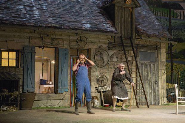 Christian et Maria devant la niche du chien Ratatouille. Tout se joue dans la cour. Sur le toit de carton-pâte, les tuiles sont une image projetée.
