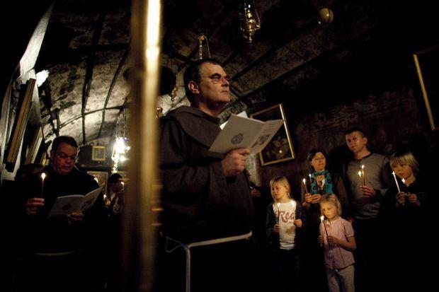 Le frère Stéphan, supérieur du couvent franciscain du Saint-Sauveur à Jerusalem, prie avec des visiteurs dans la grotte de la nativité, à Bethléem.