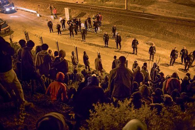 1er août, 23 h 50. De part et d'autre des barbelés, migrants et CRS se toisent. C'est le début d'un affrontement de trois heures.
