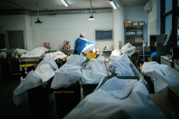 Avant la mise en bière, faute de place dans les frigos, des corps reposent sur des poubelles. Dans une entreprise de pompes funèbres, le 29 janvier.