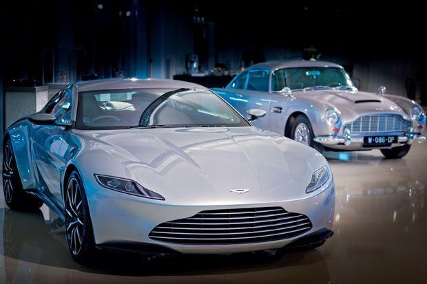 A l'arrière-plan, l'ancienne Aston Martin DB5. C'est le premier modèle à être apparu dans un « Bond ». Dans « Spectre », Daniel Craig conduit les deux bolides.