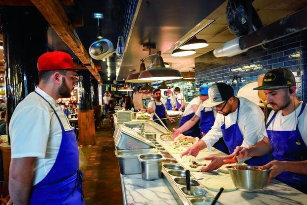 Pizzeria Popolare. Coup de feu pour l'équipe de pizzaiolos, tous napolitains. Ils travaillent devant les clients dans une cuisine ouverte.