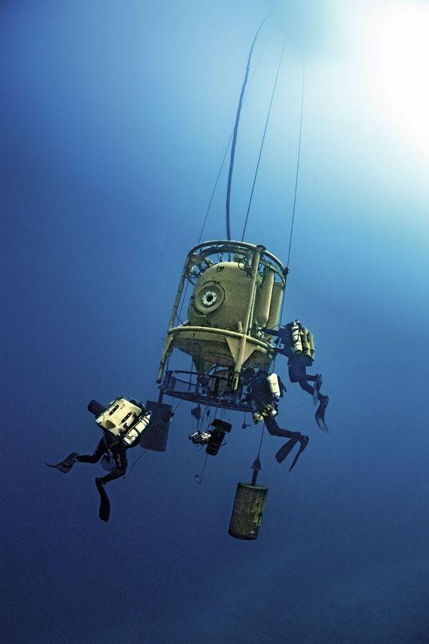 La tourelle-ascenseur est descendue et remontée par des câbles dans une eau crépusculaire. A 120mètres de profondeur, seulement 1% de la lumière solaire passe encore.