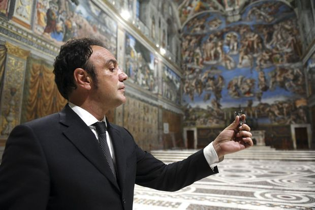 Au cœur de la chapelle Sixtine, entouré de fresques de Michel-Ange. Dans sa main : l'unique clé qui permet d'y accéder.