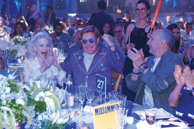 Le maître de cérémonie entouré de Lynn Wyatt, jet-setteuse richissime, et Pete Townshend, le leader des Who.