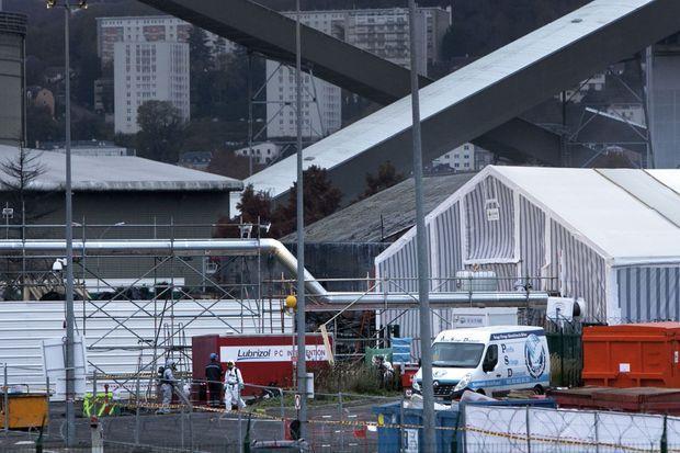 A dr., la tente de décontamination. A g., une palissade de 3 mètres de hauteur entoure le secteur brûlé. A l'arrière-plan, les tuyaux d'une sucrerie et, de l'autre côté de la Seine, des immeubles de la rue Moïse.