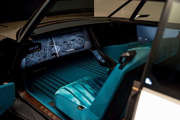 Accueillis sur des sièges au velours turquoise et au moelleux vintage, les passagers font face à un écran au format XXL, une fois le volant disparu sous la barre de son. Vive la voiture autonome !