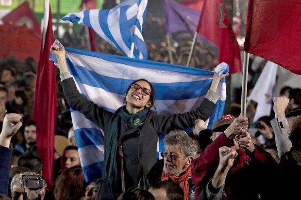Au milieu des bannières rouges du parti Syriza, une jeune femme brandit fièrement un drapeau grec.