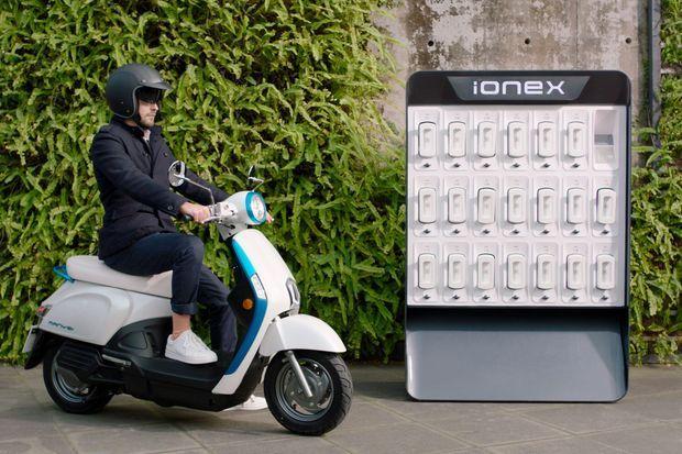 Un scooter électrique Kymco à côté d'une station de recharge permettant également l'échange ou la location de batteries.