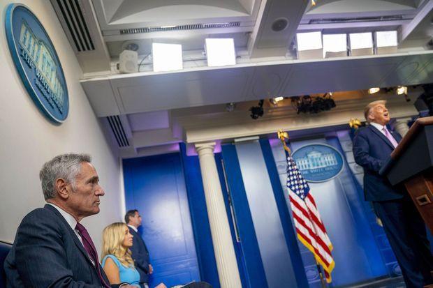 Scott Atlas, à gauche, écoute le président Donald Trump lors d'une conférence de presse à la Maison-Blanche, le 11 août dernier.