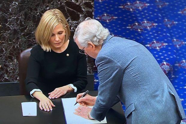 """Le sénateur McConnell signe le """"livre de serment""""."""