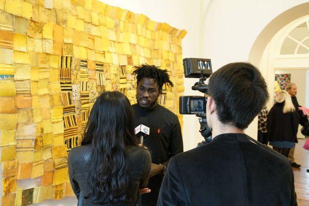 """L'artiste Serge Attukwei Clottey, jeune artiste ghanéen devant son """"Packed comunity"""" exposé par la galerie 1957"""