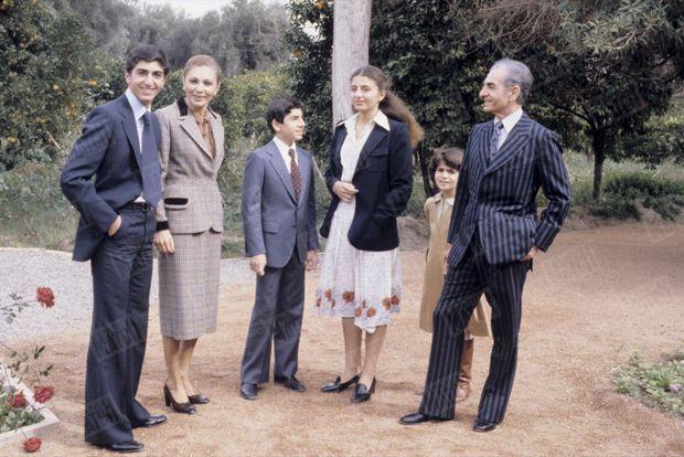 """""""Sa famille se serre autour de lui. Dans les jardins du palais """"Djenane el Kebir"""", mis à sa disposition par le roi Hassan II, le Shah au milieu de sa famille enfin réunie : de g. à dr. le prince héritier Reza, 18 ans, la Shahbanou, le prince Ali Reza, 13 ans, la princesse Farahnaz, 15 ans, et le Shah qui cache la princesse Leïla, 9 ans."""" - Paris Match n°1550, 9 février 1979."""